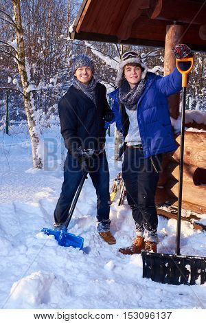 Two friends shoveling snow from the yard in winter cottage.