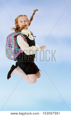 Happy girl schoolgirl in black dress and white shirt and a knapsack on his shoulders. She jumps, hands up. Turning sideways to the camera.On the pale blue background.