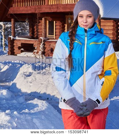 Young girl spend winter holidays at mountain cottage.