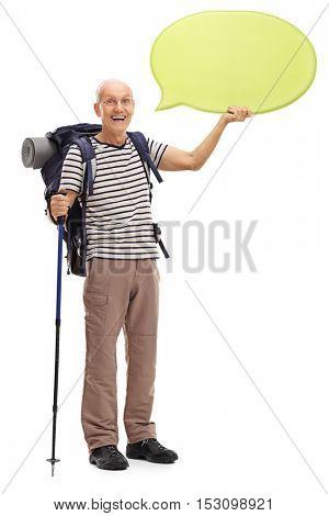 Full length portrait of a cheerful mature hiker holding a speech bubble isolated on white background