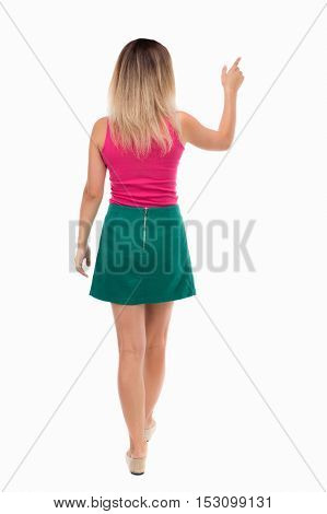back view of pointing walking  woman. going girl pointing.  backside view of person.  Rear view people collection. Isolated over white background. Girl in a green skirt goes away pointing forward.