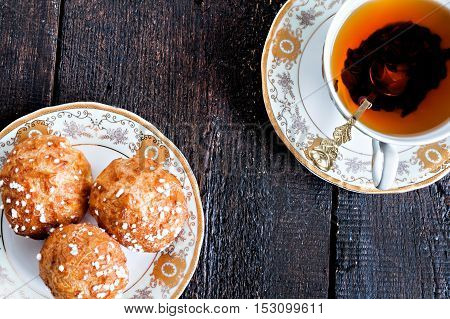 Profiteroles Topped With Sugar And Vintage Cup With Tea On A Dark Background
