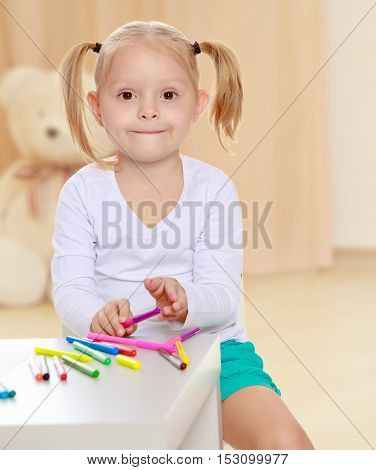 The concept of preschool development of the child , against a child's room where in the background a Teddy bear.Pretty little blonde girl drawing with markers at the table.