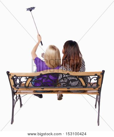 Back view two women to make selfie stick portrait sitting on the bench. Rear view people collection. backside view person. Isolated over white background. couple girls photographed using selfie stick