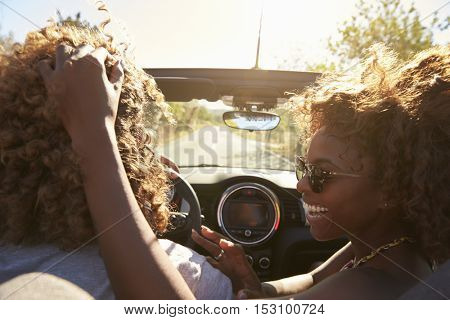 Woman embraces her partner as he drives, close up, Ibiza