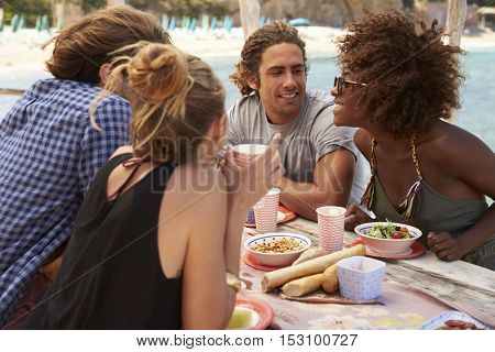 Two couples sitting at a table at the seaside, Ibiza, Spain