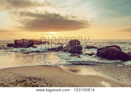Sea coast after sunrise with rocks, blue water and sunny sky, natural seasonal summer hipster background