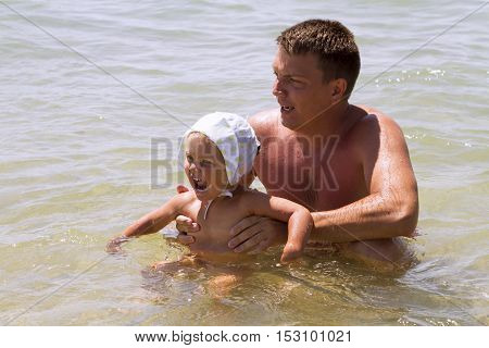 man father and daughter a little girl swimming in the sea in the waves splashing happiness joy laughter summer vacation