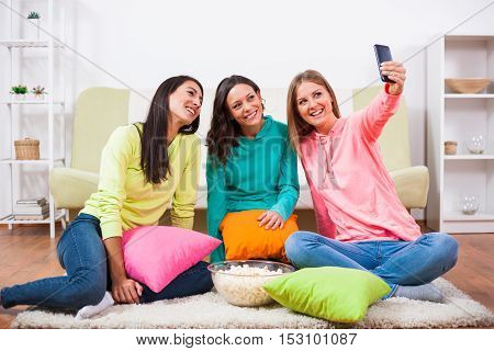 Three friends are sitting in room and taking selfie.