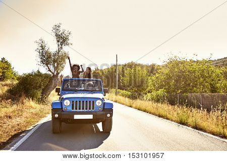 Four friends on the road in open car, two women standing
