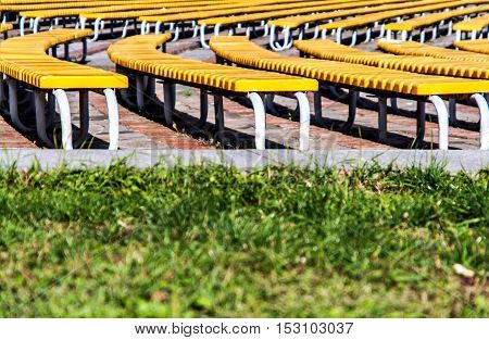 neat rows of green benches on a background of green grass