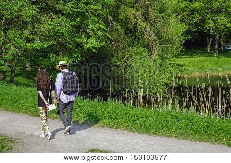 a happy young couple walking in summer park holding hands with a pond on side
