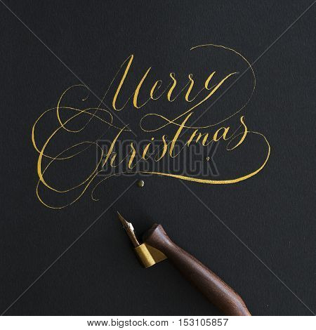 The inscription Merry Christmas calligraphy in gold ink on the greasy paper. shot from above.