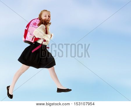 Pretty little girl schoolgirl in white blouse and black skirt to hurry to school. She jumps over the obstacle.On the pale blue background.