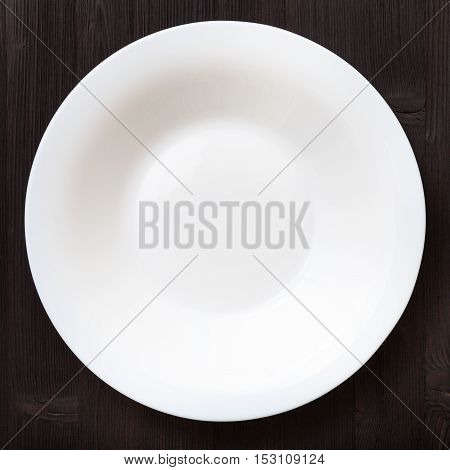 Above View Of White Deep Plate On Dark Brown Table