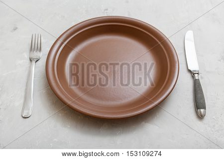 Brown Plate With Knife, Spoon On Gray Concrete