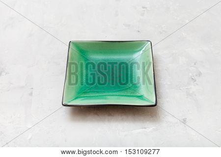 Green Square Saucer On Gray Concrete Board