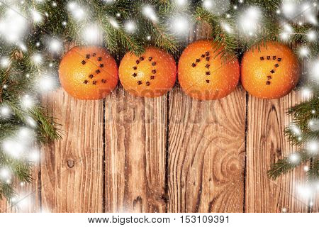 Christmas decorations with oranges and numbers of cloves on a wooden background