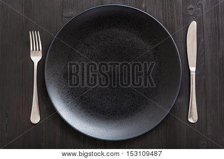 Top View Of Black Plate With Knife, Spoon On Dark