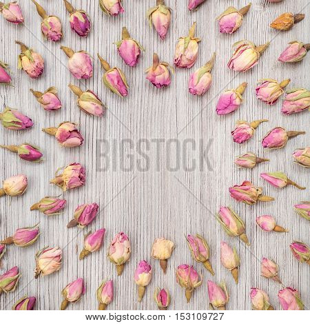Round Frame From Rose Flower Buds On Wooden Plank