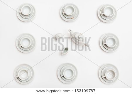 Top View Of Cups With Saucers And Teapot On White