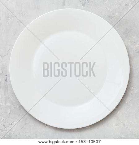 Top View Of White Plate On Gray Concrete Surface