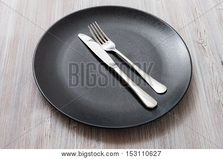 Black Plate With Parallel Knife, Spoon On Gray