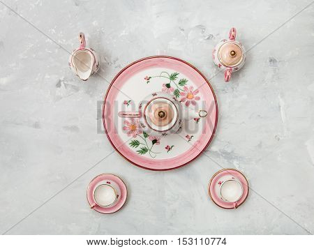 Above View Of Pink Porcelain Tea Set On Concrete