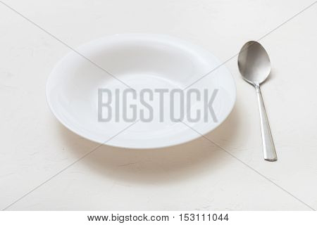 White Deep Plate And Spoon On Plaster