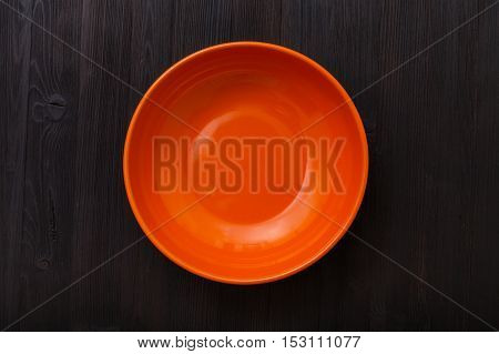 Top View Of Orange Bowl On Dark Brown Table