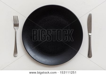 Top View Of Black Plate With Knife, Spoon On White
