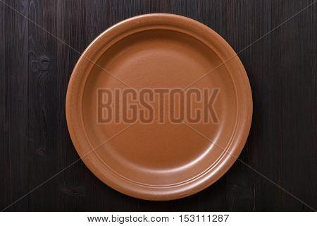 Top View Of Brown Plate On Dark Brown Table
