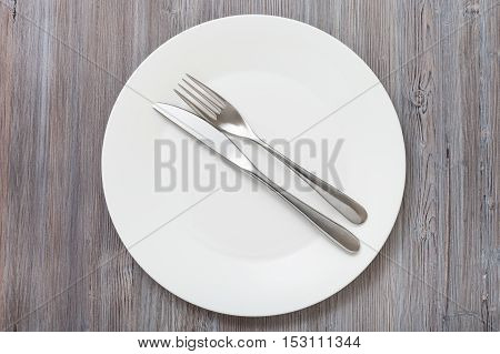 Top View Of White Plate With Flatware On Gray