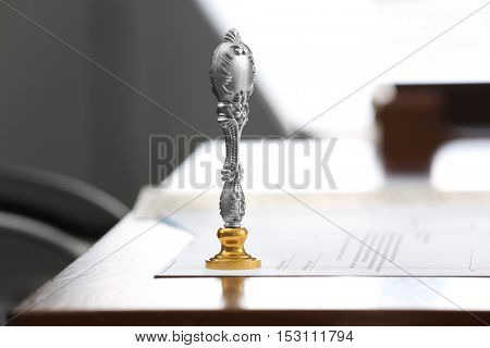 Metal stamp and document on notary public table