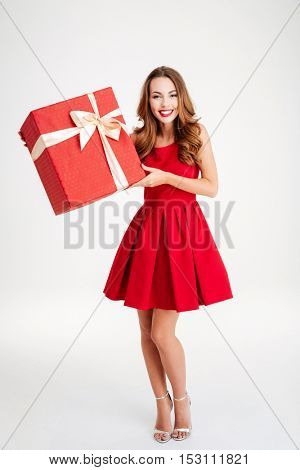 Full length portrait of a happy woman in red dress holding gift box isolated on a white background