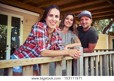 Close-up shot of three happy friends standing on the terrace of the resting house and chatting. Spending time together, laughing