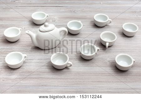 White Ceramic Cups And Teapot On Gray Brown Table