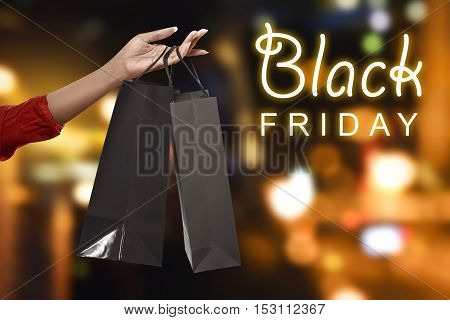 Hand Holding Black Shopping Bags