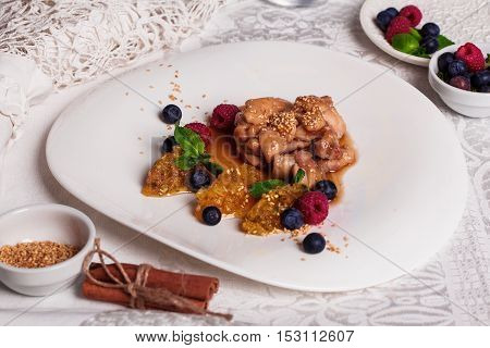 Chicken teriyaki sauce with raspberry and blueberry, quenelle of orange, natyumorort, sweet and sour sauce