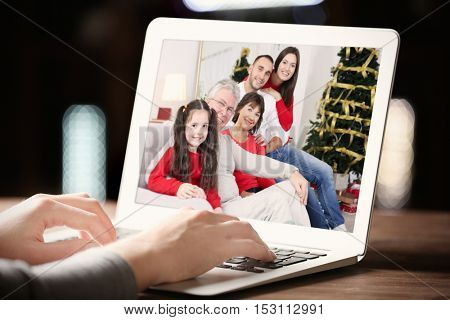 Woman video conferencing with family on laptop. Video call and chat concept. Modern communication technology.