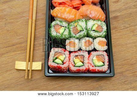 Japanese sushi and chopsticks on the wooden background. horizontal photo.