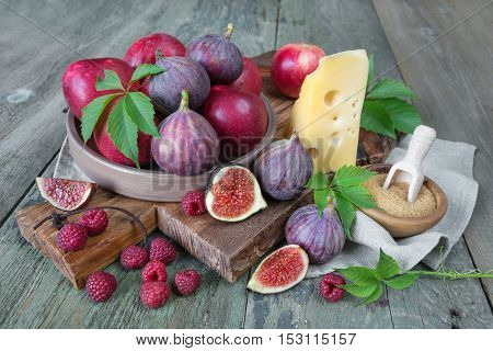 Ripe figs red raspberry and apples cane sugar and cheese are on old cutting board as well as green leaves lie on the old wooden table