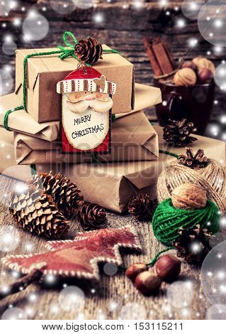 wrapping Christmas presents on an old wooden background in rustic style with bokeh effect