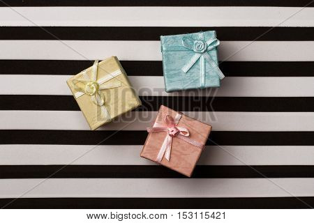 top view of colored gift boxes on black and white stripes background