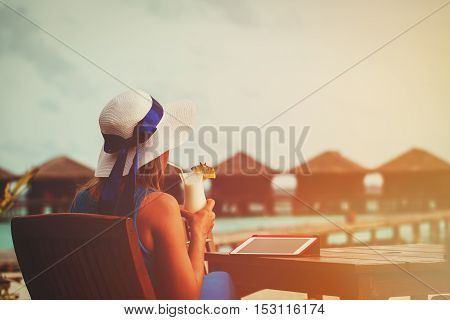 young woman with cocktail and touch pad at luxury tropical resort