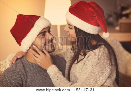 Young couple in Santa Claus hats resting at home