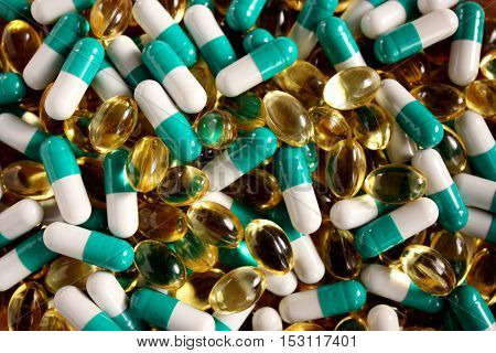 A scattering of tablets of different shapes and colors. Advertising a Healthy lifestyle, but also the possibility of  addiction to the medication and excess dosage. Horizontal.