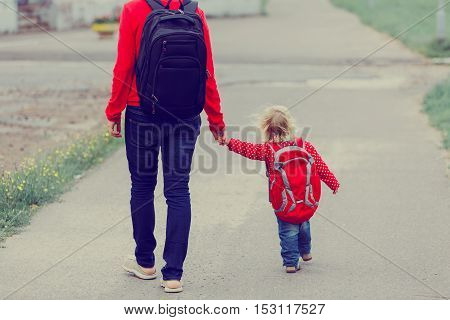 Mother holding hand of little daughter with backpack going to school or daycare