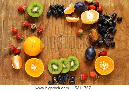 Various berries on a wooden table. Strawberry, mandarin, kiwi, grapes.
