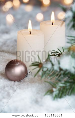 Two white Christmas candles with pine branches in the snow